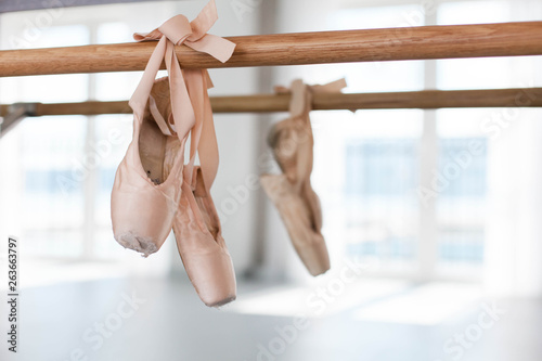 Valokuva Old pointe shoes hang on ballet wooden barre in dance class room