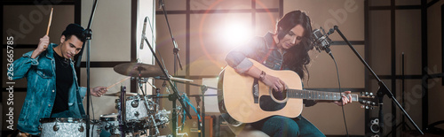 Fotografie, Tablou  panoramic shot of attractive woman playing guitar while mixed race musician play