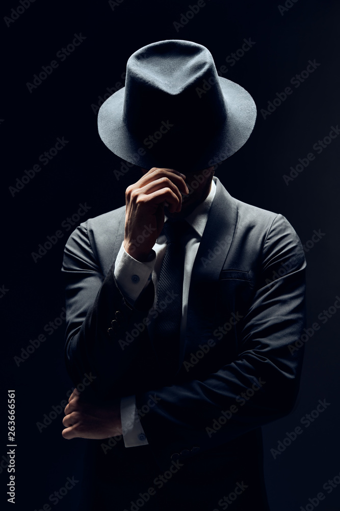 Fototapeta Man in suit hiding face behind his hat isolated on dark background