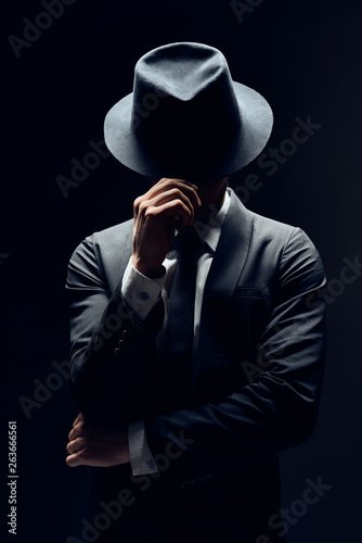 Man in suit hiding face behind his hat isolated on dark background Fototapet