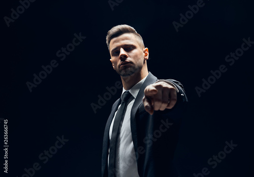 Платно Serious handsome man in black suit pointing his finger to you and camera isolate