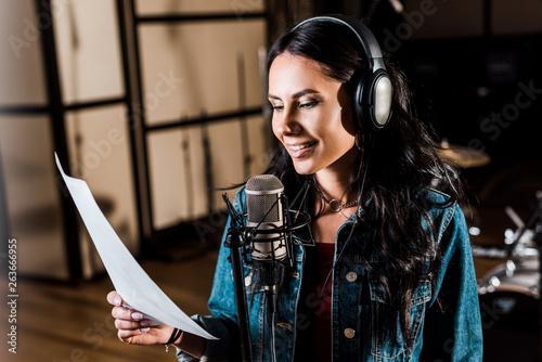 pretty woman in headphones singing in recording studio near microphone - 263666955