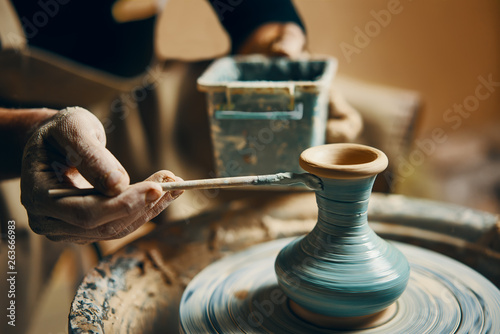 Fotografia Man painting handmade pottery at ceramic workshop