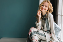 Beautiful Young Woman With Long Blonde Wavy Hair Sitting On Window Sill In Room With Turquoise Wall. She's Smiling And Enjoying Morning Time. Wearing Nice Pajama.