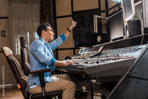 Fototapeta  smiling mixed race sound producer showing thumb up while working at mixing conso