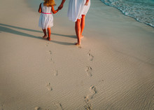 Mother And Kids Walking On Beach Leaving Footprint In Sand