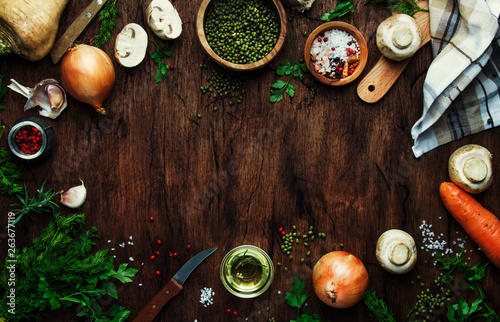 Food cooking frame background. Ingredients for prepare green lentils with vegetables, spices and herbs, wooden kitchen table background, place for text. Vegan or vegetarian food oncept