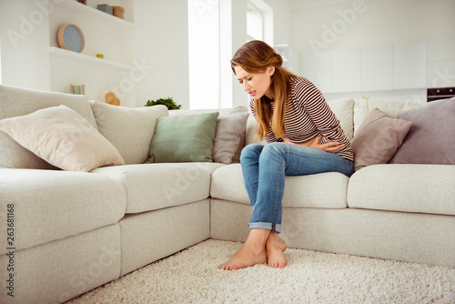 Fotografia  Portrait of upset disappointed lady sit divan touch tummy had indigestion food p