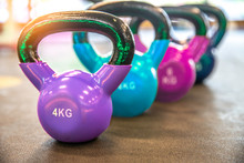 Colorful Kettlebells In A Row On  Floor In The Gym