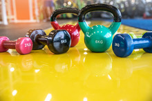 Multi-colored Dumbbells And Kettlebells  On A Yellow Background In Gym.