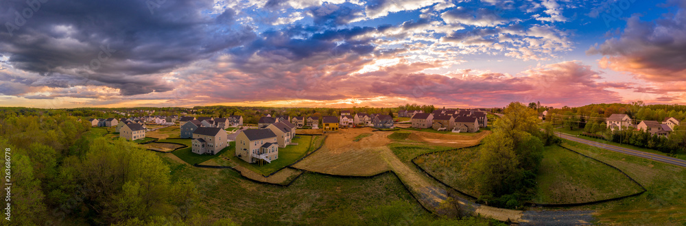 Fototapety, obrazy: Aerial sunset panorama of luxury real estate development single family house neighborhood street with dramatic sky in Maryland USA