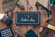 Happy Labor Day Background Concept. Flat Lay Of Construction Blue Collar Handy Tools And White Collar's Accessories Over Wooden Background With Text Happy Labor Day On Black Chalkboard.