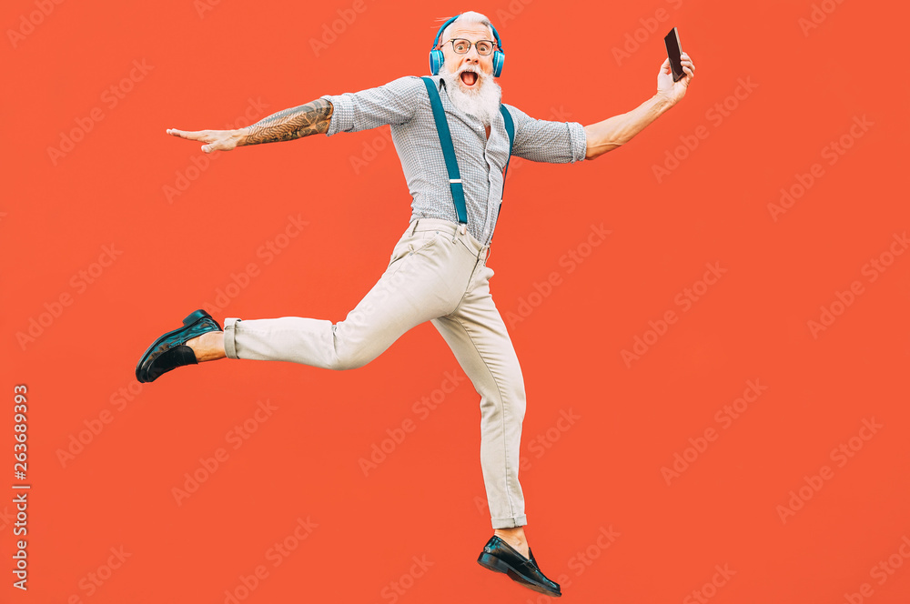 Fototapety, obrazy: Senior crazy man jumping while listening music outdoor - Hipster male having fun dancing and celebrating life outside - Happiness, technology and elderly lifestyle people concept