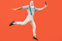 Senior Crazy Man Jumping While Listening Music Outdoor - Hipster Male Having Fun Dancing And Celebrating Life Outside - Happiness, Technology And Elderly Lifestyle People Concept