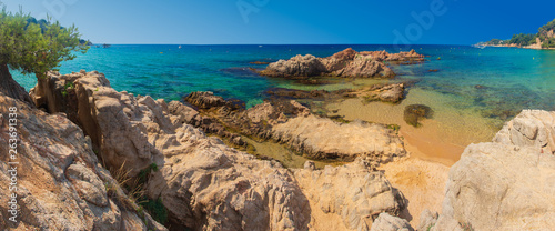 Blue lagoon in Costa Brava with rocks on sand beach Cala Treumal Fototapet