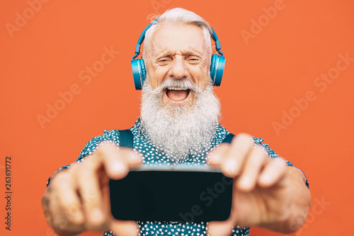 Fotografie, Obraz  Senior bearded man making selfie with mobile phone while listening to his favori