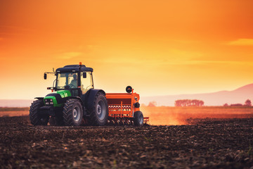 Beautiful sunset, farmer in tractor preparing land with seedbed cultivator