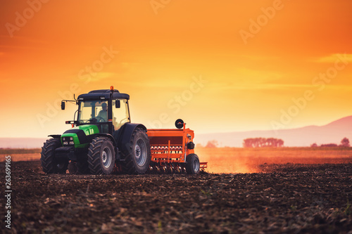 Fotografia  Beautiful sunset, farmer in tractor preparing land with seedbed cultivator