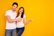 Leinwandbild Motiv Close up photo beautiful she her he him his pair wondered direct indicate fingers empty space sale discount great little low price wear casual jeans denim white t-shirts isolated yellow background