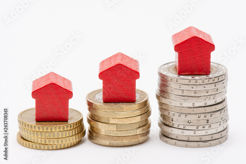Trois piles de pièces de monnaie en euro, surmontées de petites maisons rouges e Wallpaper Mural
