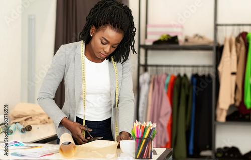 Fashion designer working in studio, cutting drawing Fototapeta