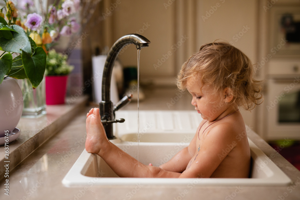 Fototapeta Baby taking bath in kitchen sink. Child playing with foam and soap bubbles in sunny bathroom with window. Little boy bathing. Water fun for kids. Hygiene and skin care for children