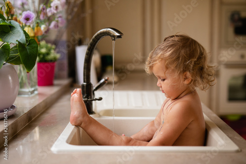 Baby taking bath in kitchen sink Wallpaper Mural
