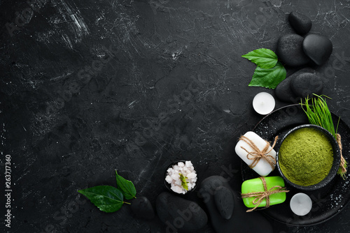 Zen stones and leaves with water drops. Spa background with spa accessories on a dark background. Top view. Free space for your text.