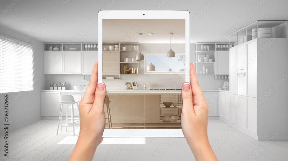 Fototapeta Hands holding tablet showing modern white and wooden kitchen, total blank project background, augmented reality concept, application to simulate furniture and interior design products