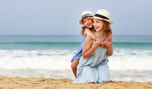 Happy Family At Beach. Mother And Child Daughter Hug At Sea