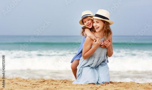 fototapeta na ścianę happy family at beach. mother and child daughter hug at sea