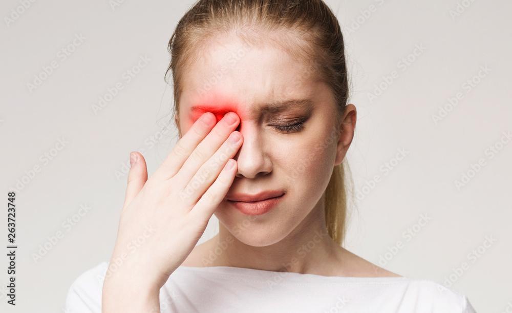 Fototapeta Upset woman suffering from strong eye pain