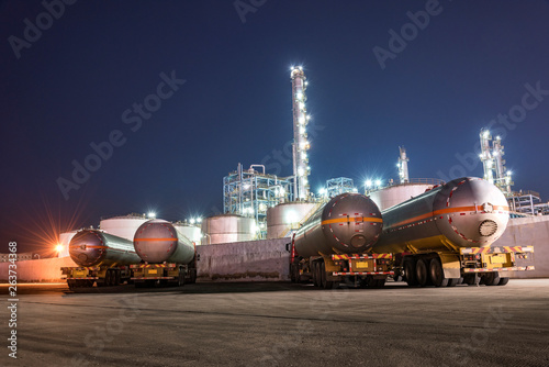Fotografie, Obraz  The oil truck tankers in the refinery background in the evening