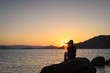 Silhouette of a girl on the background of the sunset by the sea