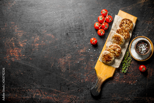Cutlets on paper with spices,thyme and tomatoes. - 263742326