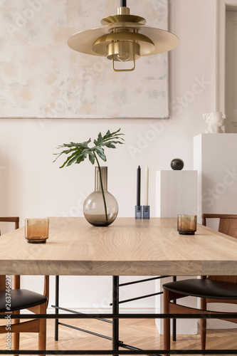 Fotografia, Obraz  Eclectic and elegant dining room interior with design sharing table, chairs, gold pedant lamp, abstract paintings and stylish accessories