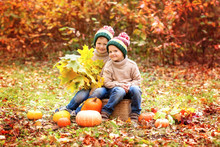 Two Boys Sitting On A Pumpkin In The Autumn Forest . Halloween