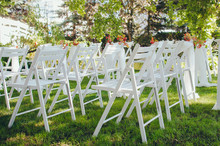 Wedding Set Up. Ceremony In The Bosom Of Nature. White Chairs With Flowers Set In The Grass