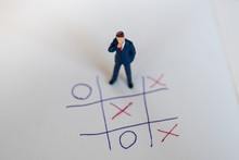 Business Direction And Planning Concept. Businessman Miniature Figure Standing And Thinking On Paper With OX (tic Tac Toe) Board Game.