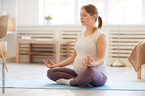 Fotografia  Full length portrait of pregnant woman sitting in lotus position while meditatin