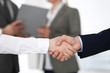 Business people shaking hands at meeting or negotiation, close-up. Group of unknown businessmen and women in modern office at background. Teamwork, partnership and handshake concept