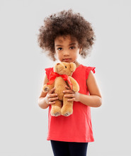 Childhood And People Concept - Sad Little African American Girl With Teddy Bear Toy Over Grey Background