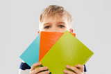 school, education and people concept - little student boy t hiding behind books over grey background - 263782362
