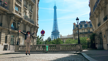 Fototapeta na wymiar Young stylish happy woman walking the Camoens Avenue street rising hands and turning with eiffel tower on the background in Paris