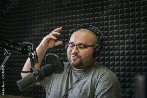 Fényképezés  Smiling and gesturing radio host with headphones on his head reading news from p