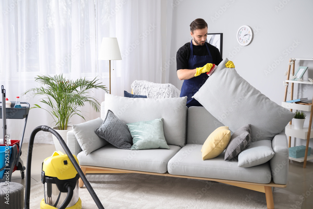 Fototapety, obrazy: Male janitor cleaning sofa in room