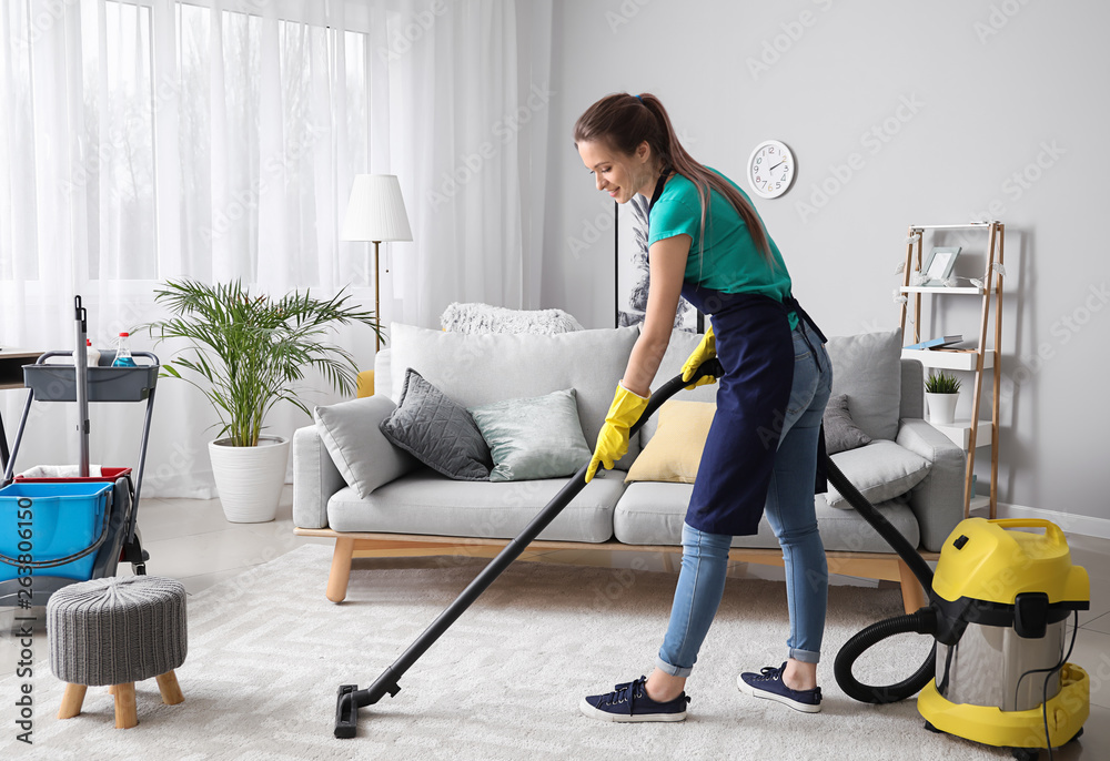 Fototapety, obrazy: Female janitor with vacuum cleaner in room