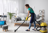 Female janitor with vacuum cleaner in room