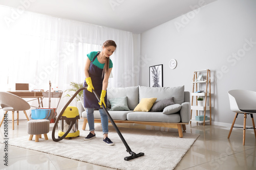 Fotografía Female janitor with vacuum cleaner in room