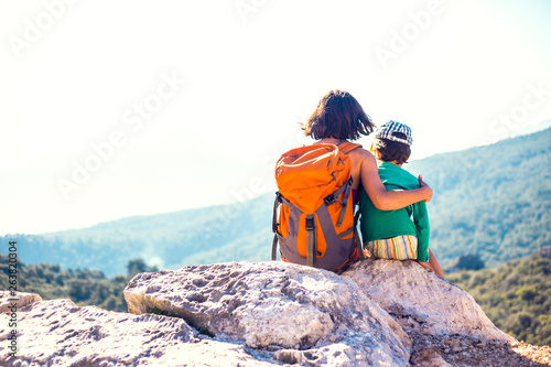 The boy and his mother are sitting on the top of the mountain. Wallpaper Mural